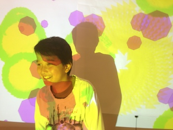 kid with generative art projected