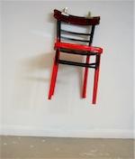 Une chaise rouge et noire accrochée à un mur